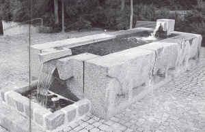 Tonstung stenskulptur af en brønd, formet som en rektangel med vandhave i den ene ende, og vandfald i den anden. Skal symbolisere kvægdrift der før i tiden foregik på de højtliggende områder på skovbakken og bejsebakken, ned til de lavereliggende områder, hvor kvæget kunne vandes.