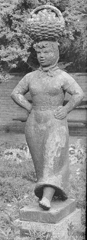 Bronzeskulptur af en kone som går stolt, med knyttede hænder i siden og en stor kurv med æg balancerende på hovedet