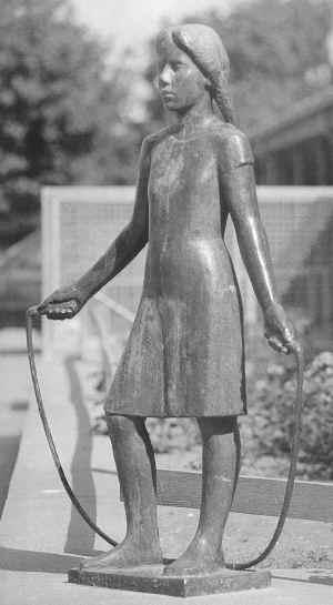 Bronzeskulptur af en langhåret lille pige iført kjole, med bare fødder, som sjipper med sjippetov