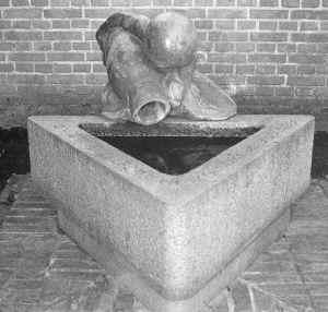Skulptur af en dreng med krukke som forsøger at øse vand fra en trekantet brønd