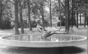 Bronzeskulptur af en badende pige ved navn susanne som har kastet sig baglæns midt i en cirkulær pool